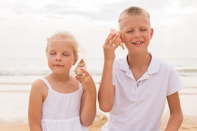 Brother and sister holding a seashell.