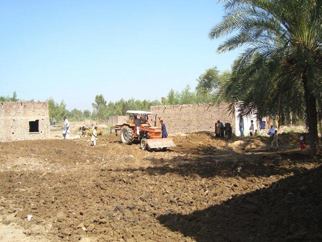 Photograph of a tractor in a Lunda village field, having freshly prepared the soil for cultivation after the 2010 flood.