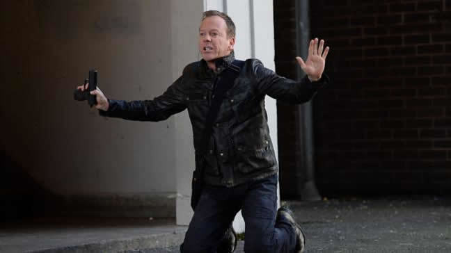 Jack Bauer kneels on the ground in a back street with his hands up. He holds a gun in one hand.