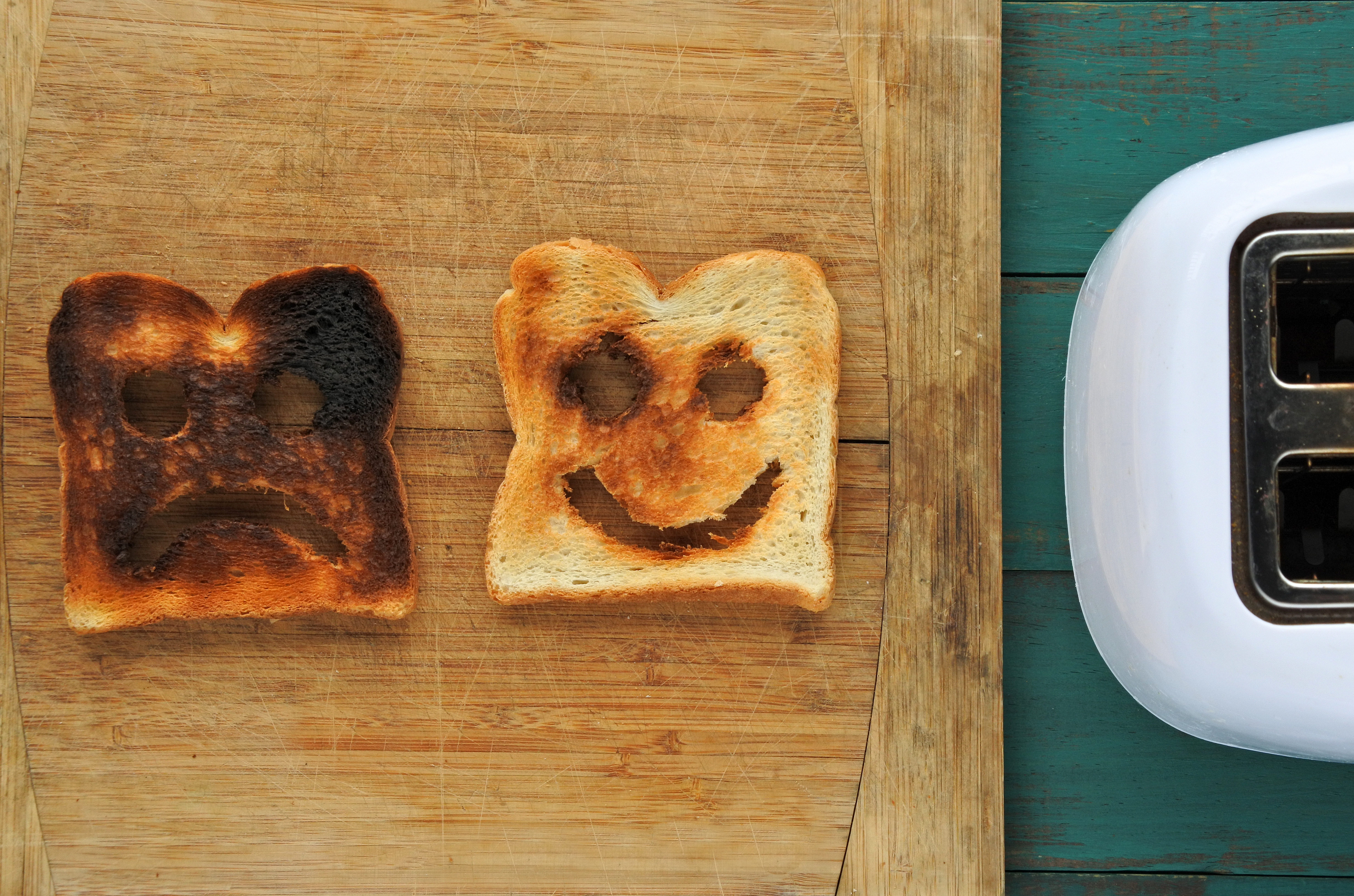 two pieces of toast on a table by a toaster, one black and dark brown (burned) with a sad face carved into it, one paler brown and white with a happy face carved into it