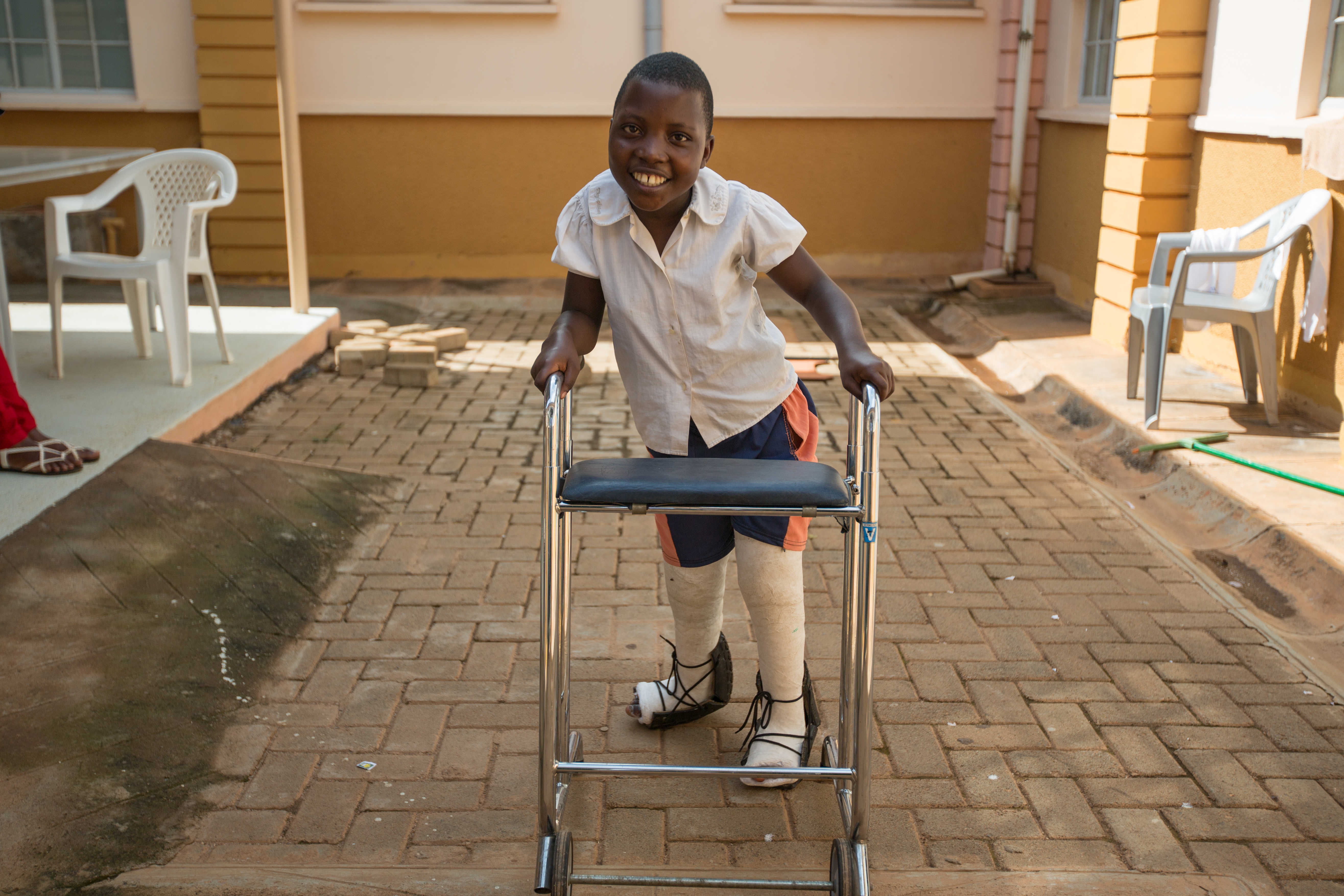 A girl with casts on her legs is using a walking frame. She is smiling as she walks towards the camera
