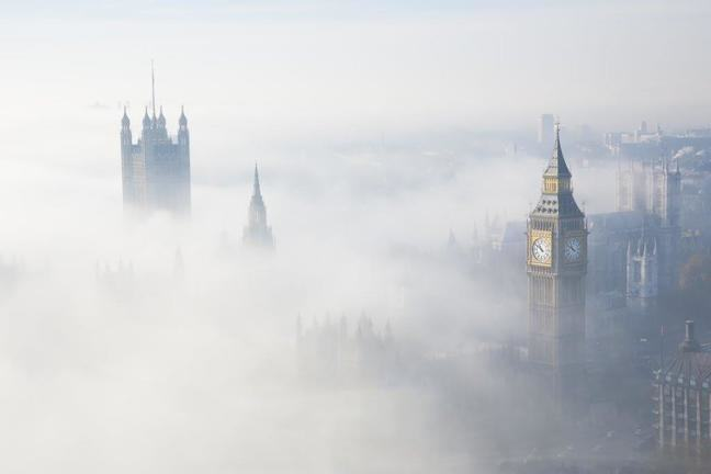 Photograph of London from above with the tops of Big Ben and Westminster poking out through shallow fog