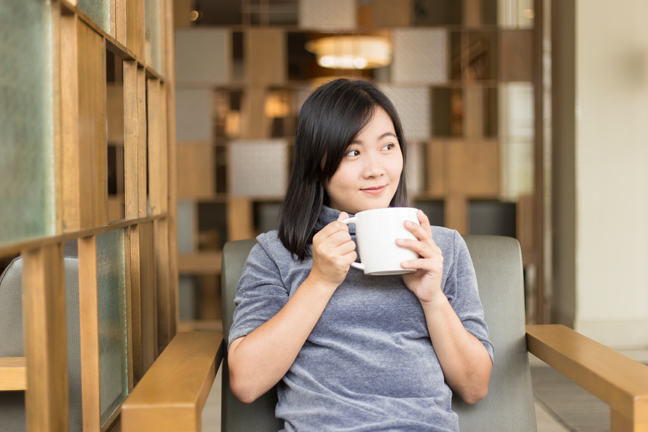 Woman drinking coffee in the morning at a cafe.