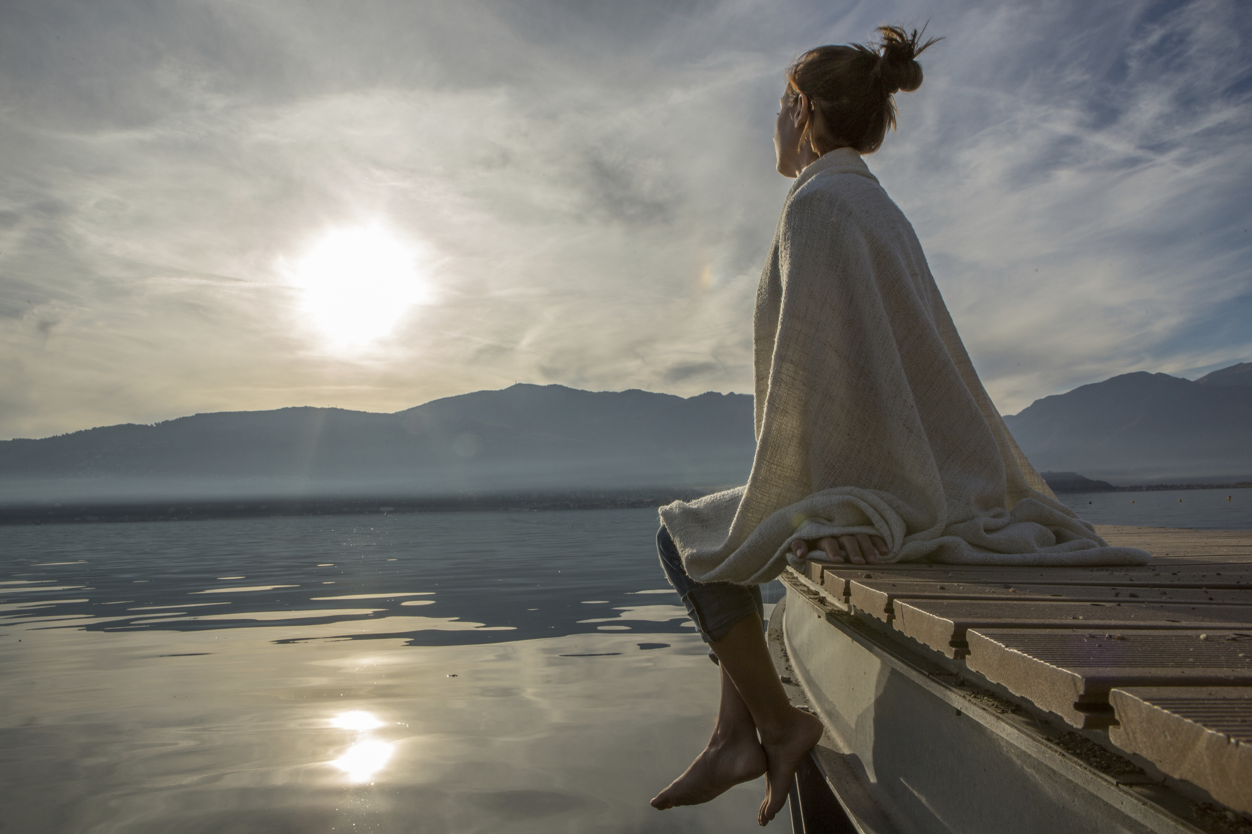 a contemplative scene of a young woman gazing out over a lake