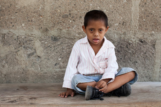 A young boy with Down syndrome sitting crossed legged on the floor.
