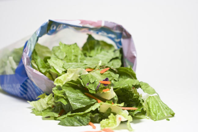 bag of salad, opened, with leaves spilling out
