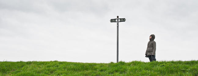 a woman looking up at a cross roads sign