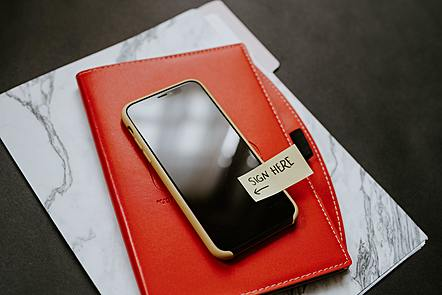 "Smart phone placed on top of a red notebook. On the phone is a sticker saying ""Sign Here"". Photo by Kelly Sikkema on Unsplash"