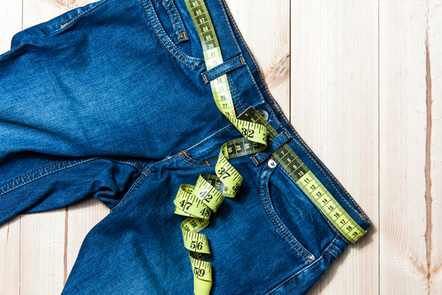 Jeans and tape measure on a wooden background.
