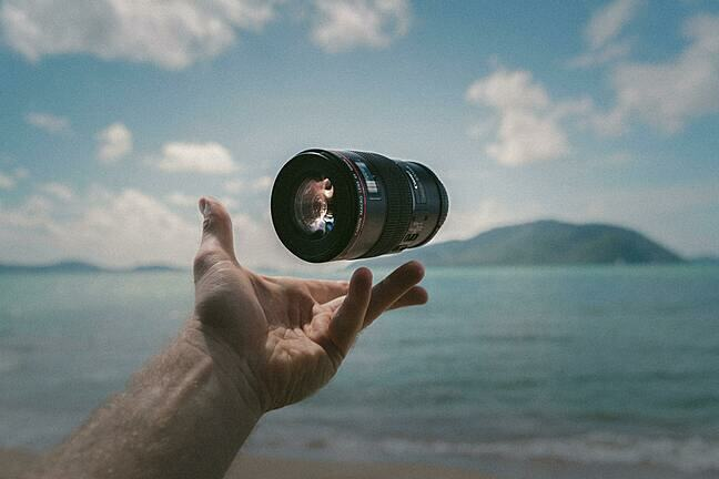 A camera lens floating above a hand. The background is out of focus but appears to be of a beach and the sea.