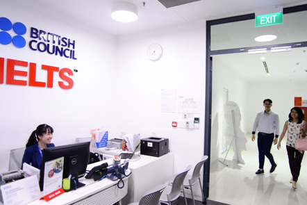 reception desk at an IELTS centre. Two candidates are entering.