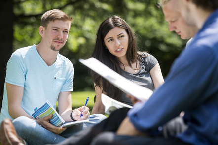 Three students sit in the sunshine, discussing and making notes