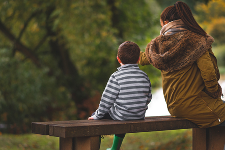 A mother and child sitting next to each other on a park bench.