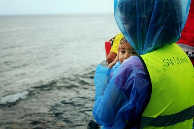 A female volunteer wearing a blue plastic poncho covering her arms and head and a yellow vest that says Siri Anne on the back of it holds a tiny baby. It is raining and the volunteering is looking out to sea.
