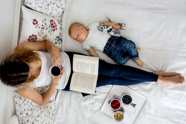 A woman sitting on her bed reading a book and drinking a coffee with a baby lying next to her.