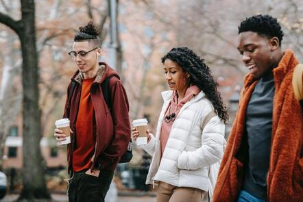A group of young people walking with coffee cups in hand, they are all wearing bright orange coats and jumpers.