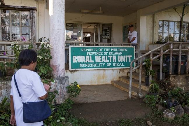 A woman is about to visit walk up the steps to a rural health unit in Philippines