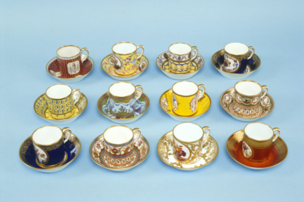 A collection of 12 cups and saucers, painted with decoration in different colours