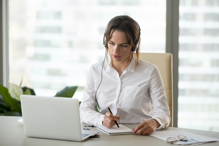 Woman in white shirt is watching something on a laptop while wearing headphones. She holds a pen and notepad for taking notes.