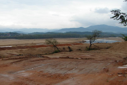 Reddish ground which is composed on weathered laterite deposits in the foreground - ion adsorption deposits. Mountains in the background.