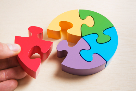 A circular jigsaw puzzle of multi-coloured pieces with a hand inserting the final piece.