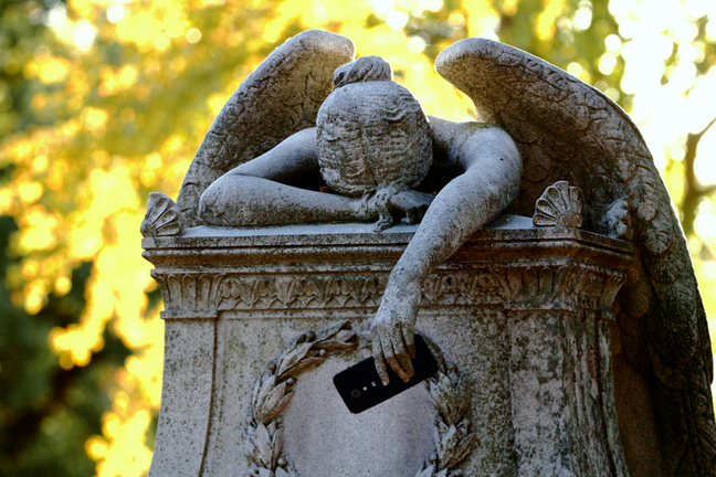 A monumental angel slumped over a tomb, clutching a mobile phone.
