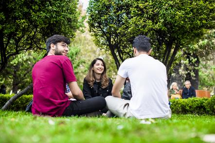 Three people talking on the grass