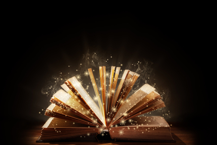 Open book on black background. Light and sparkles coming from pages