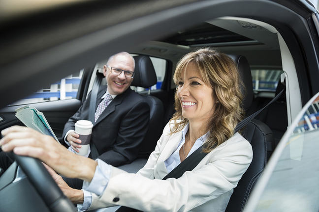 Smiling business people carpooling in car
