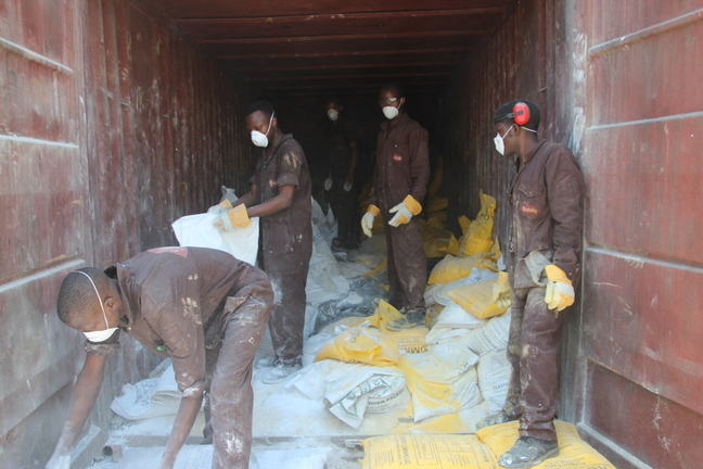 Workers handling broken bags with the lead powder mix.