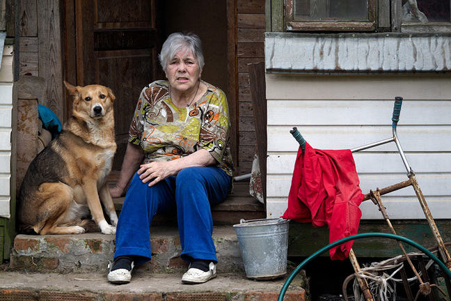 elderly woman with her dog sitting on door step