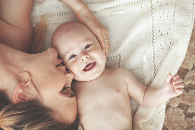 A portrait of a mother lying on a rug with her 3 month old, smiling baby.