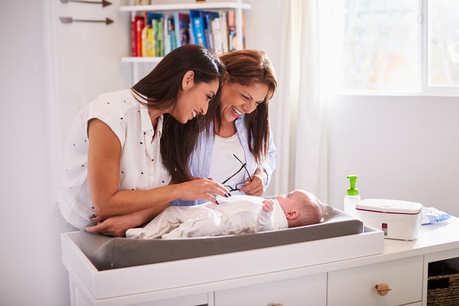 A woman and her mother looking at her baby on a changing table.