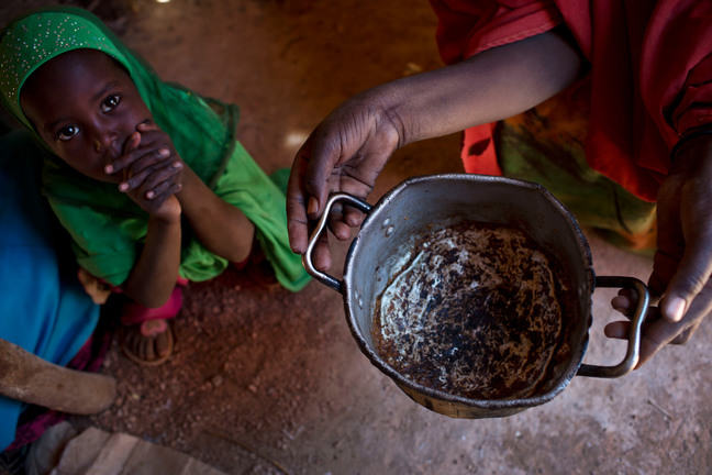 A child sits crouched on the ground with hands clasped looking up at a woman holding an empty pot of food.