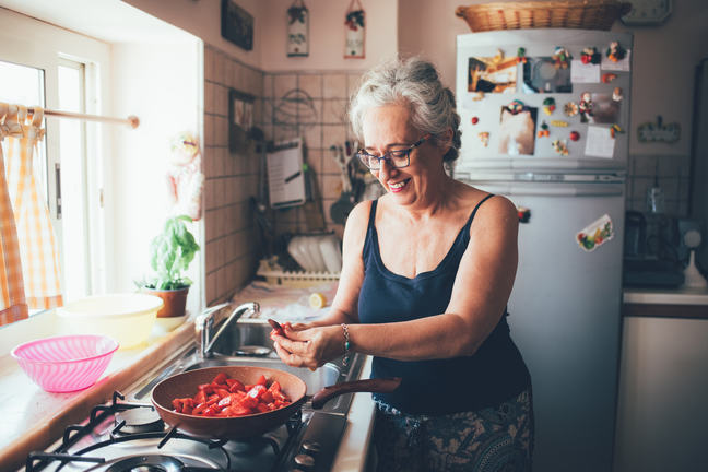 Woman chopping tomatoes into saucepan smiling