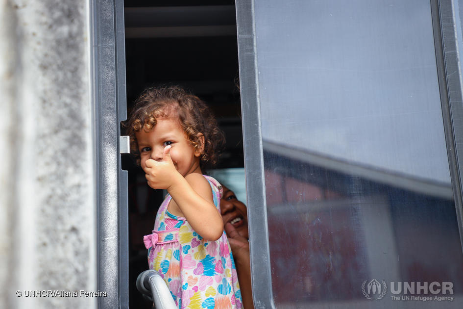 Young girl looks out of window with her thumb up smiling.