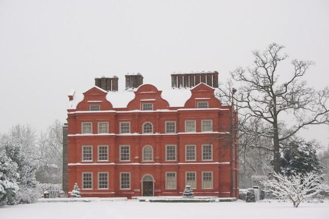 A photograph of Kew Palace in winter. The grounds and rooftop are covered in snow.