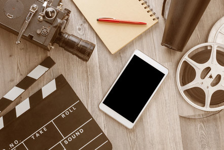 Film-making artefacts, camera, clapperboard, film reel, notepad and loud hailer with smartphone in centre