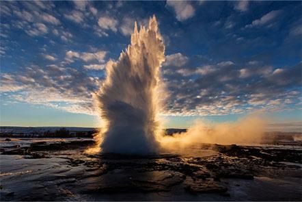 A geyser erupting at sunrise.