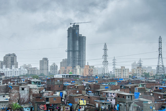 Mubai slums with skyscrapers in background.