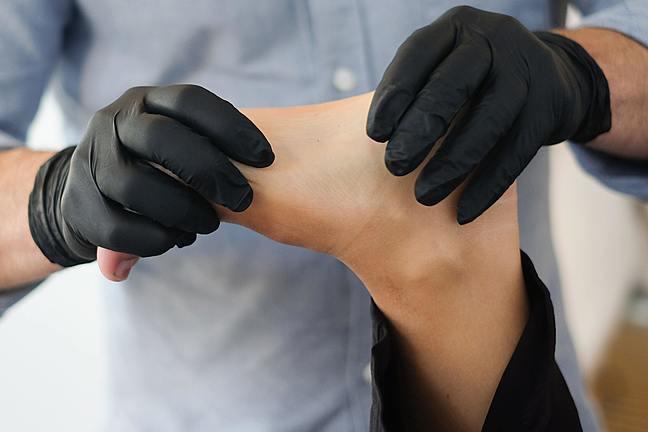 Man wearing gloves rehabilitating a foot
