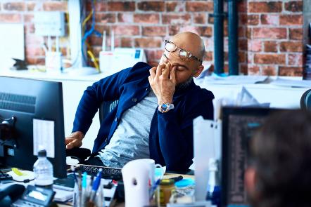 Man sat at a desk rubbing his eyes