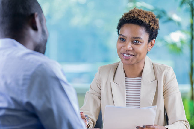 Businesswoman conducts job interview Confident African American businesswoman interviews a man for a position in her company. She is holding the man's resume