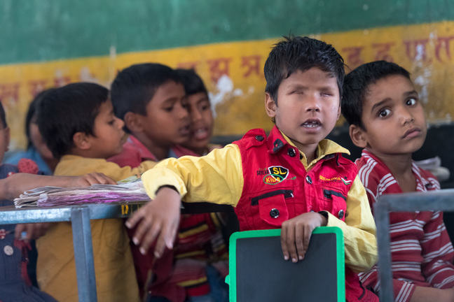 A boy born without retina is sitting with classmates at school. He is resting a hand on a chair as he turns towards the camera.