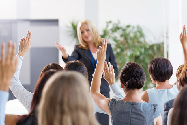 Female executive standing before an audience of staff with raised hands taking questions.