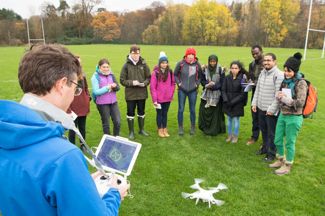 Group of students gathered around a drone about to take off in a field