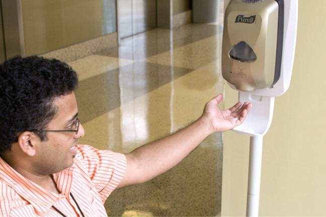 Медицинский работник с поднятой рукой, чтобы получить очищающий лосьон для рук из дозатора