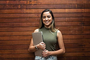A young new graduate woman stands holding a laptop and smiling