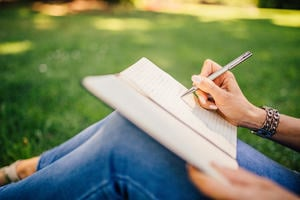 Person sitting on the grass writing in a notebook