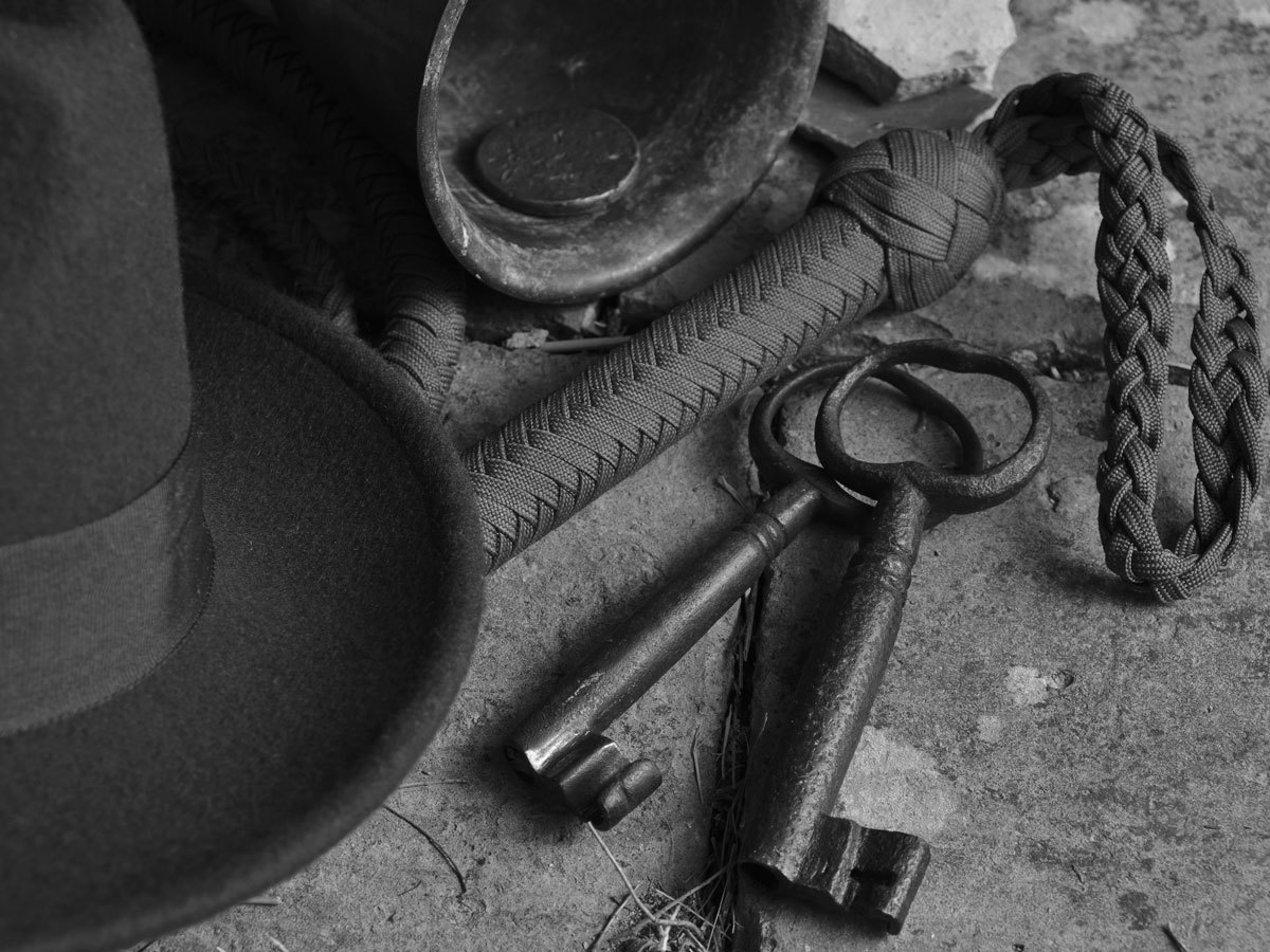 Fedora hat, bullwhip, rusty keys and coin in a leather cup on a concrete floor
